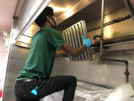 Service Technician cleaning an exhaust system