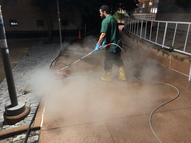 A CKC technician pressure washes a sidewalk