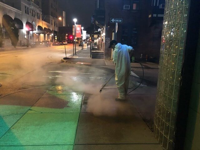 A CKC technician uses a pressure washer to remove gum and dirt from a sidewalk