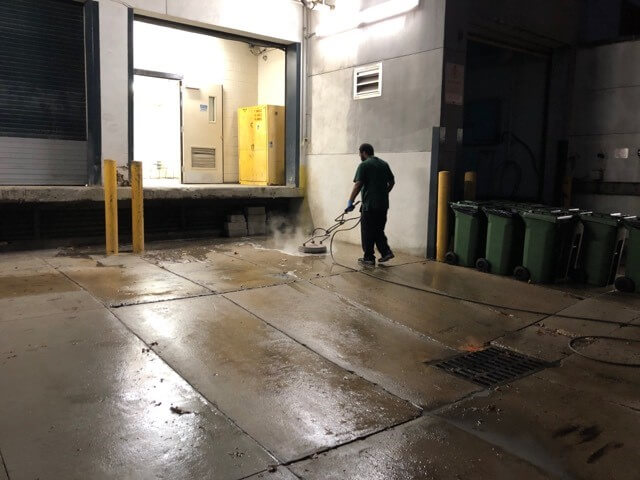 A CKC technician cleans a loading dock